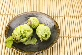 image of butterbur  - Harvested green butterbur sprouts in the plate on twig place mat - JPG