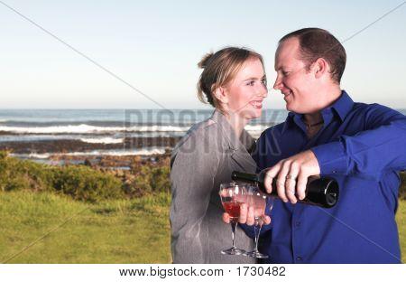 Couple Next To The Coast Drinking Wine