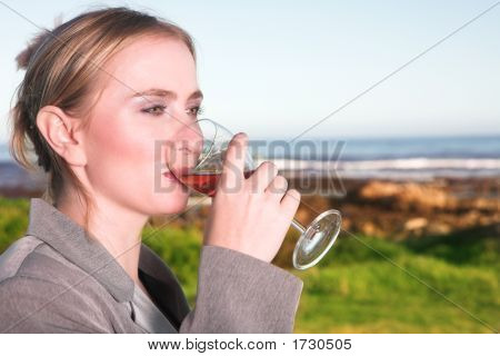 Woman Drinking Wine Next To The Ocean