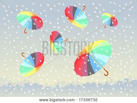 cinco guarda-chuvas coloridos voando em cidade grande. está chovendo.