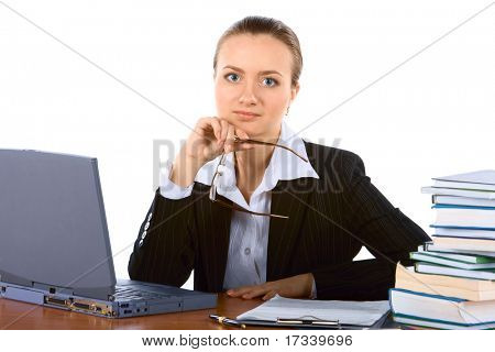 young successful businesswoman at table with laptop and spectacles in hand