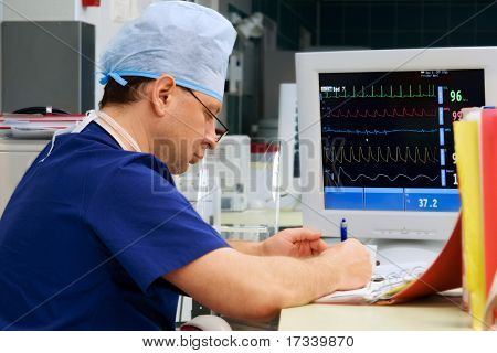 doctor in ICU writing prescription with monitor