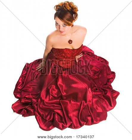 young attractive woman sitting in long red dress. view from abobe.