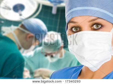 Doctora en la sala de operación con los cirujanos sobre fondo