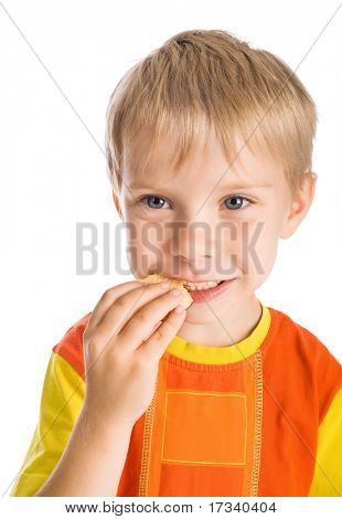 smiling five-year-old boy eating cookie isolated on white