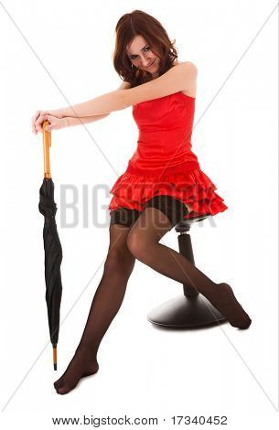 youn attractive woman in red dress sitting on chair with umbrella