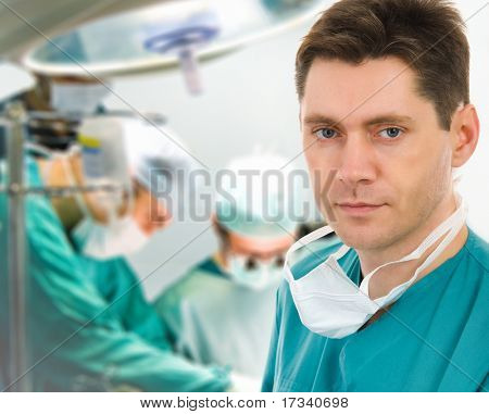 Male surgeon with two doctors on background in operation room