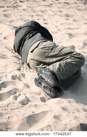 homeless man sleeping on sand