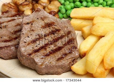 Beef steaks with chips, peas and button mushrooms.