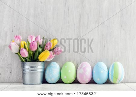 Easter eggs and a spring bouquet of tulips on a wooden table. Springtime decoration.
