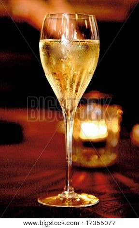 Single bocal of champagne close-up over red background