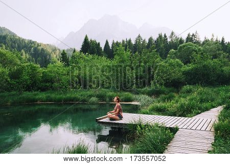poster of Woman Doing Yoga And Meditating In Lotus Position On The Nature.