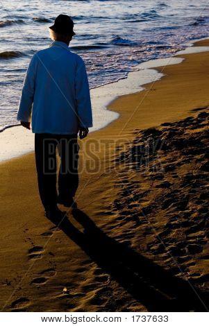 Old Man Walking On The Beach.
