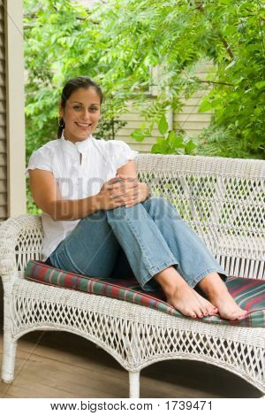 Young Woman Relaxing On The Porch