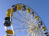 image of ferris-wheel  - interesting perspective shot of a ferris wheel against a clear blue sky - JPG