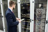 Technician holding clipboard while analyzing server in server room poster