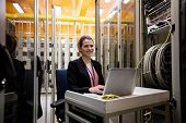 Portrait of technician using laptop while analyzing server in server room poster