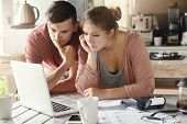 Serious Man And Woman Sitting At Kitchen Table In Front Of Open Laptop Computer, Looking At Screen W poster