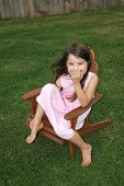 stock photo of lawn chair  - little girl sitting in lawn chair laughing - JPG