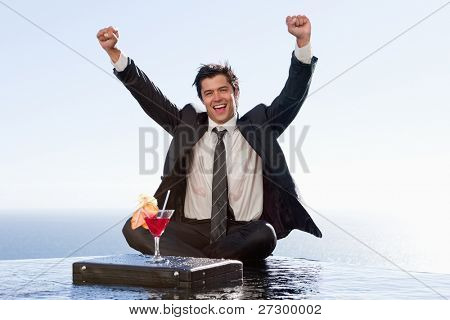 Businessman relaxing with a cocktail and his fists up in a swimming pool