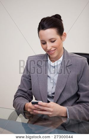 Smiling young businesswoman sitting behind desk writing a textmessage