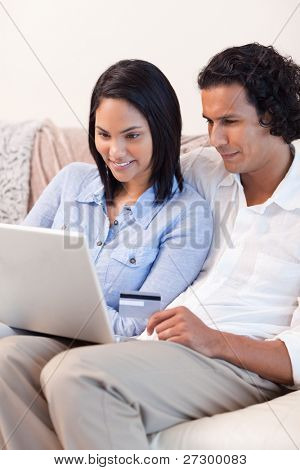 Young couple booking holidays online together