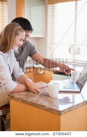 Portrait of a couple having tea while using a laptop in their kitchen