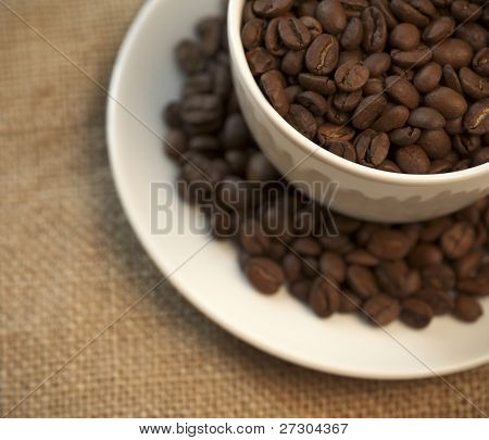 Macro studio shot of a cup of coffee beans.