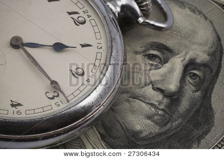 time is money concept of cracked and dusty antique pocket watch on US currency