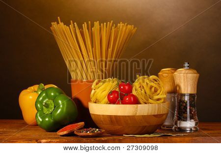 spaghetti, noodles in bowl, paprika tomatoes cherry on wooden table on brown background