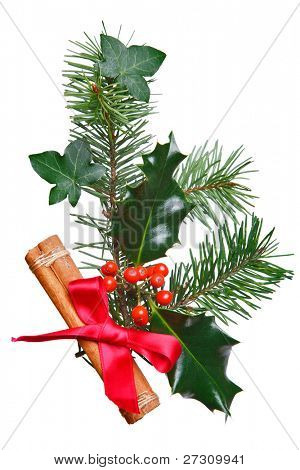 Photo of a Christmas decoration made with holly, red berries, spruce, ivy and a cinnamon stick with red bow, isolated on a white background.