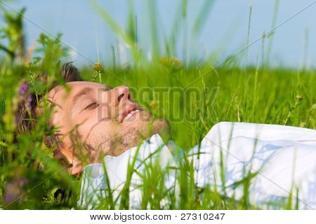 Young man laying on a lawn or meadow in summer and is dreaming or sleeping