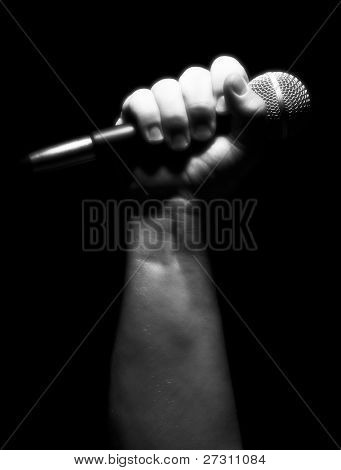 Gray Scale Vertical Microphone Clinched Firmly in Male Fist on a Black Background.