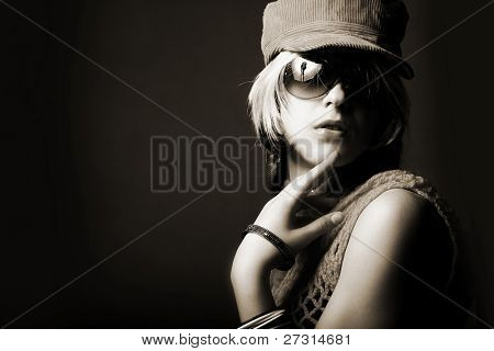 Fashion woman portrait wearing sunglasses on dark background
