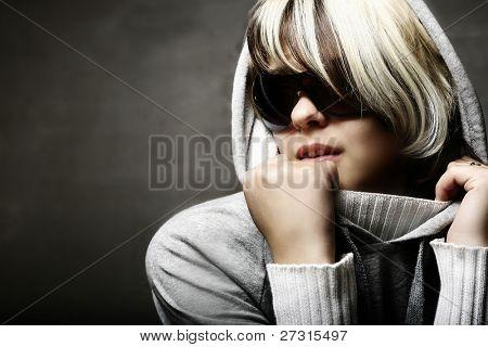 Fashion woman portrait wearing sunglasses on dark background