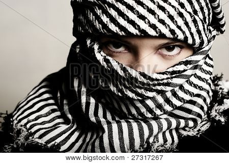 Close-up portret of a terrorist, who has covered her face with a scarf.