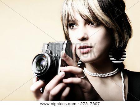 Joven hermosa mujer tomar una foto con una cámara retro