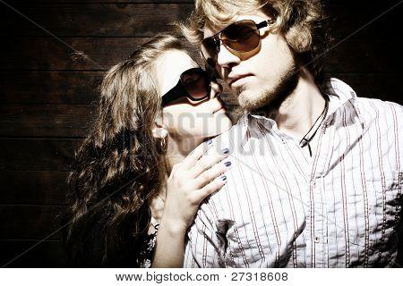 戴着太阳镜孤立的 grunge 背景上的时尚年轻夫妇