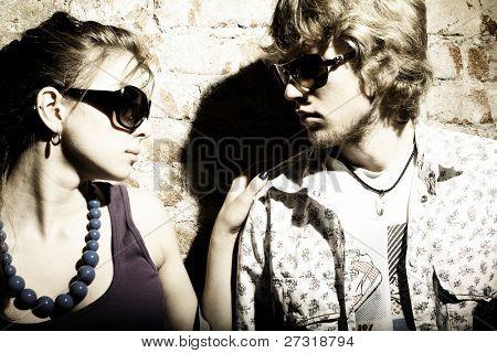 Casal jovem elegante, usando óculos escuros, isolados no fundo grunge