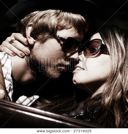 Loving couple embraces in the car. Art photo