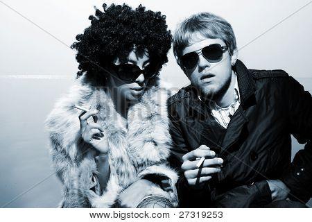 Fashionable young couple wearing sunglasses  smoke a cigaret