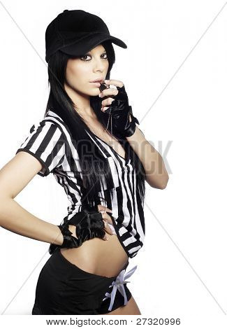 Sporty attractive young woman in ref black and white costume uniform blowing whistle