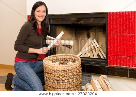 Young woman putting wood logs from wickerwork basket into fireplace