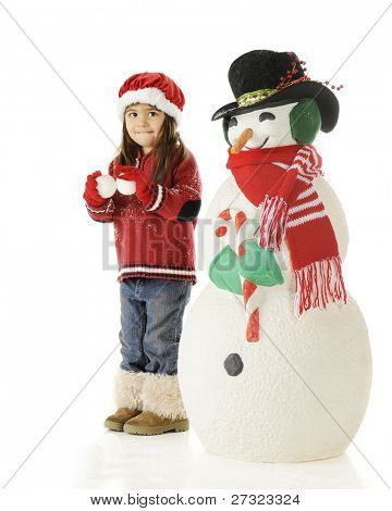 "An adorable preschooler standing ready for ""war"" holding 2 snowballs and ready, if necessary, to duck behind a large Christmasy snowman nearby.  On a white background."