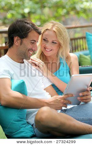 Pareja relajarse en el sofá con tableta electrónica