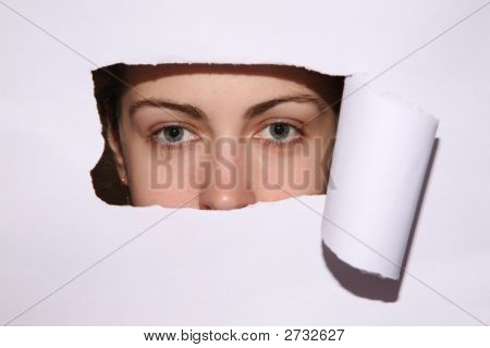 Woman Looks In The Hole Of The Sheet Of Paper