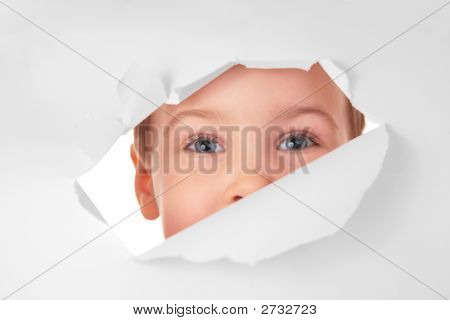 Child Looks In A Hole In A Sheet Of A Paper