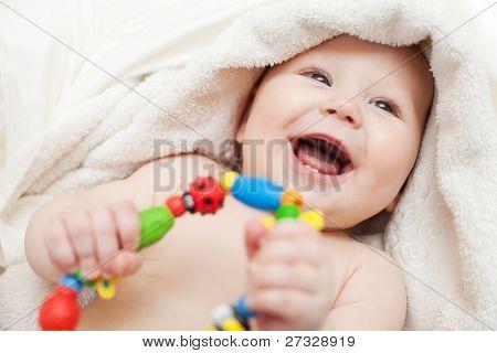 kleines Lächeln Baby mit einem Spielzeug