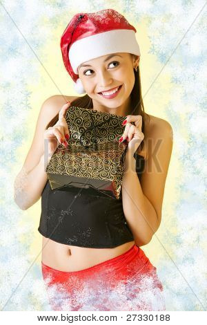 Winter Portrait von eine schöne junge lächelnde Frau mit einem Geschenk in ihren Händen