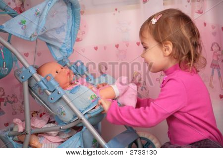 Small Girl With The Doll In The Carriage